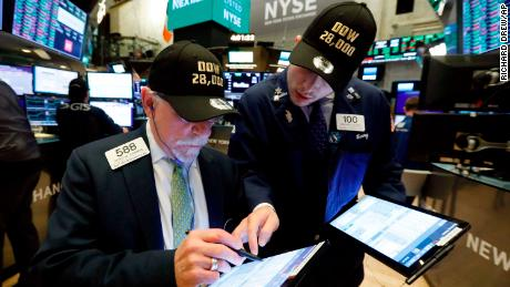 "Traders Peter Tuchman, left, and his son Benjamin Tuchman, wear ""Dow 28,000"" hats at the close of trading on the floor of the New York Stock Exchange, Friday, Nov. 15, 2019. The Dow Jones Industrial Average added 222 points, or 0.8%, to 28,004. (AP Photo/Richard Drew)"