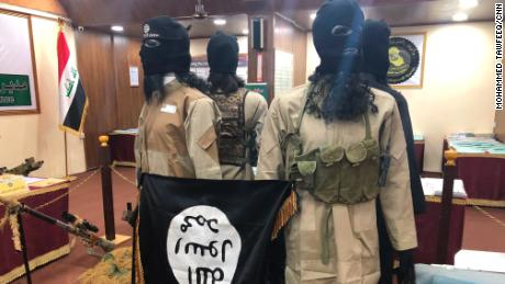 Models of ISIS soldiers hold their flag upside down.