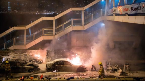 Firefighters put out a burning car set on fire by protesters near Hong Kong Polytechnic University in the Tsim Sha Tsui district on November 18.