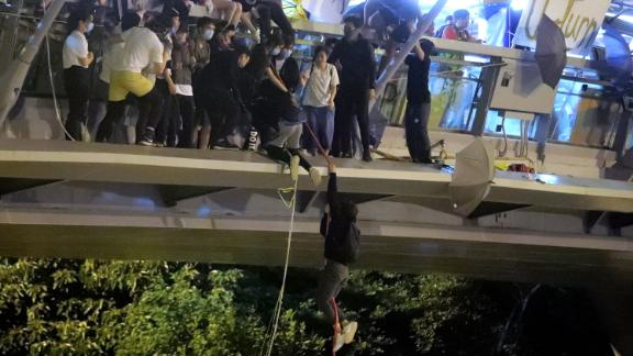 Protesters use a rope to lower themselves from a pedestrian bridge to waiting motorbikes to escape from police at Hong Kong Polytechnic University on November 18.