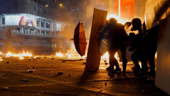 Protesters react as police fire tear gas in the Kowloon area of Hong Kong, Monday, November 18.