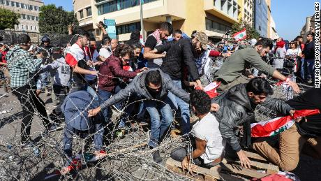 Lebanese protesters flee from security forces after having cut through the security barrier leading to the government palace at Riad al-Solh square on Tuesday.