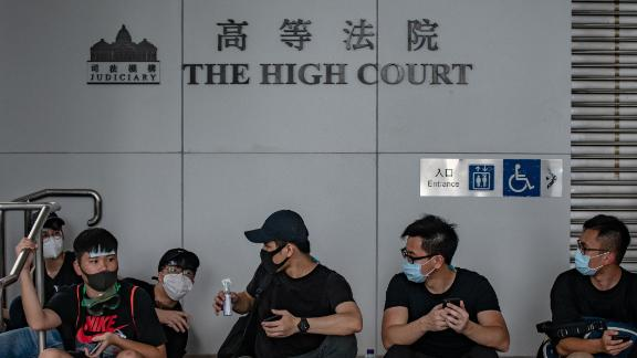 A group of protesters rest outside the High Court in Hong Kong on June 21, 2019. - Thousands of protesters converged on Hong Kong's police headquarters and blocked major roads on June 21, demanding the resignation of the city's pro-Beijing leader and the release of anti-government demonstrators arrested during the territory's worst political crisis in decades. (Photo by Philip FONG / AFP)        (Photo credit should read PHILIP FONG/AFP via Getty Images)
