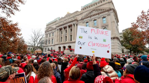 Thousands of teachers wearing red surround the Indiana Statehouse in Indianapolis on Tuesday.