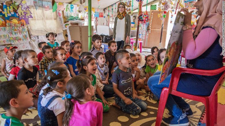"Children listen to a teacher read a ""Sesame Street"" story in a class at an International Rescue Committee classroom in an informal tented settlement for Syrian refugees."