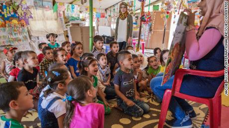 "Children listen to a teacher read a ""Sesame Street"" story in a class at an International Rescue Committee classroom in an informal tented settlement for Syrian refugees."