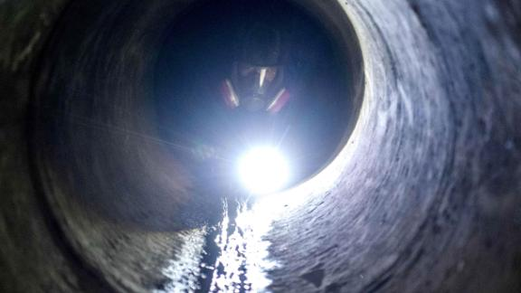 A protester uses a flashlight while crawling through a sewer tunnel to see how wide it is as he and others try to f