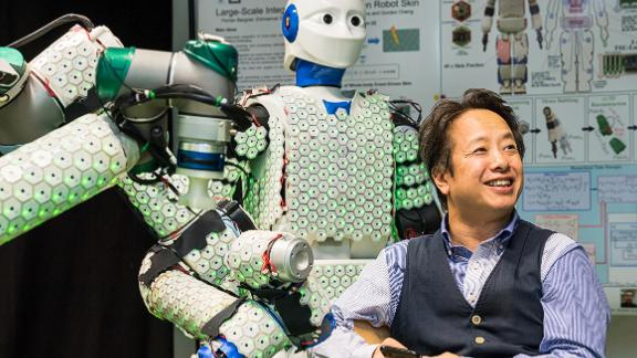 Professor Gordon Cheng with the H-1 robot, covered in 13,000 sensors that enable tactile sensation
