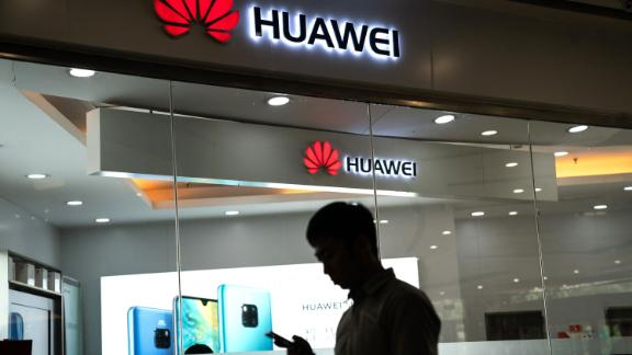 A man walks past a Huawei logo displayed at a retail store in Beijing, May 23, 3019.