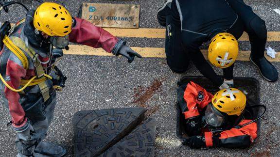 A Fire Services Department rescue diver prepares to enter the sewage system on November 20 to search for protesters who escaped from the Hong Kong Polytechnic University.