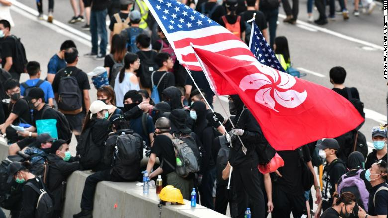 A man waves a US and Hong Kong flag while standing on a divider after he and other protesters occupied Harcourt Road while marching against a controversial extradition bill in Hong Kong on July 21.