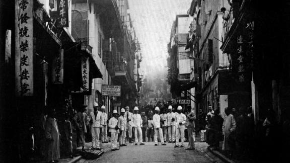 Plague inspectors on a street of Hong Kong, around 1890.