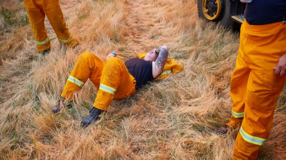 A CFA crew member rests after a day of maintaining controlled back burns in St Albans, Australia, on November 21.