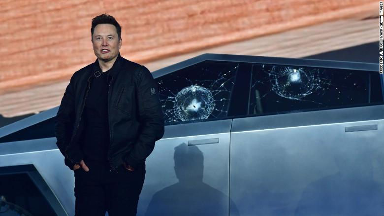 Tesla CEO Elon Musk stands in front of the shattered windows.