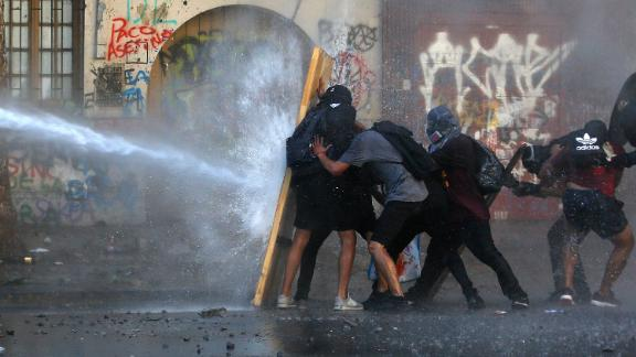 Demonstrators take cover from water fired by a riot police truck during a protest against President Sebastian Piñera on November 19 in Santiago, Chile.