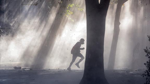 An anti-government demonstrator runs through a tear gas cloud during clashes in Santiago, Chile, on Nov. 19.