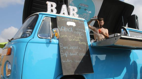 A barman serves drinks from a makeshift bar as Lebanese old Volkswagen car enthusiasts gather at a beach in the southern Lebanese town of Naqoura.