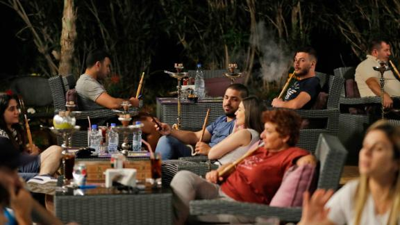 Lebanese people smoke waterpipes at a restaurant in the coastal city of Batroun north of Beirut on May 22, 2019.