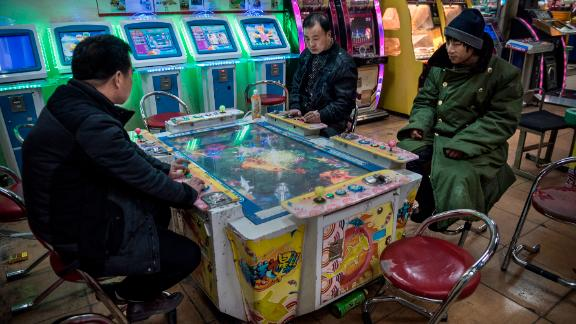Chinese men play video games at an arcade on January 20, 2015 in central Beijing.