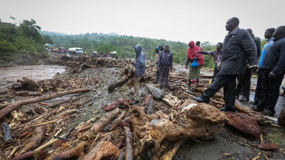 Passengers from stranded vehicles stand next to the debris from floodwaters on the road from Kapenguria in western Kenya Saturday, November 23, 2019.