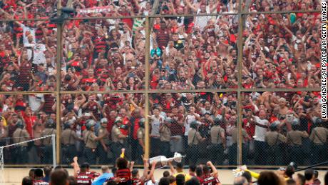 Players of Brazil's Flamengo celebrate with the trophy in front of their fans after winning the Copa Libertadores final by defeating Argentina's River Plate.