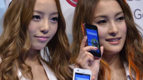 """(L-R) Koo Hara and Park Gyuri of South Korean all-girl pop group Kara pose with the new smart phone """"Optimus Bright"""", produced by South Korean electronics giant LG Electronics in Tokyo on June 17, 2011.  The Optimus bright has 4.0-inch LCD display on its thin 9.5mm body. AFP PHOTO / Yoshikazu TSUNO (Photo credit should read YOSHIKAZU TSUNO/AFP via Getty Images)"""