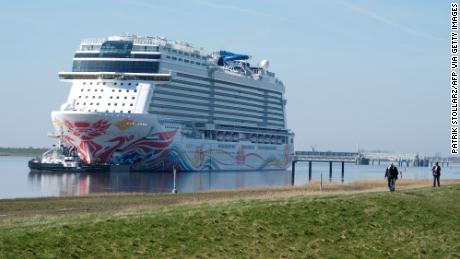 "Spectators look on as the ""Norwegian Joy"" cruise ship, previously named ""Norwegian Bliss"", makes its way over the river Ems near Emden, northern Germany, on March 27, 2017. The ship of the Norwegian Cruise Line, that was built at the Meyer Werft shipyard in Papenburg, northern Germany, is made ready to enter service. Final technical and nautical tests are due to be carried out during the following days on the North Sea. / AFP PHOTO / PATRIK STOLLARZ        (Photo credit should read PATRIK STOLLARZ/AFP via Getty Images)"