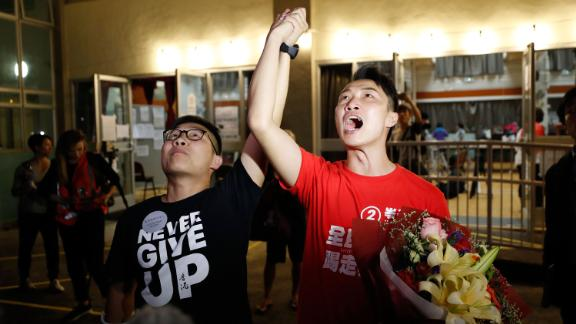 "Pro-democracy candidate Jimmy Sham, right, celebrates with a supporter after winning his election in the Sha Tin district, early November 25. ""Today's result represents (my constituency's) support to protesters. The government should immediately establish the Five Demands and respond to the public's voices,"" Sham posted on Facebook, referencing a long-standing protest slogan."