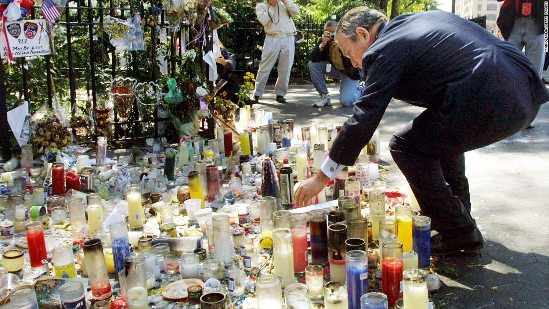 Bloomberg places a candle at a World Trade Center memorial in September 2001.