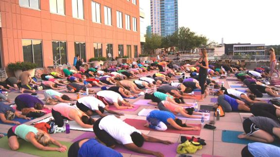A yoga class on Whole Foods Market flagship store's rooftop plaza, Lamar St., Austin, TX, 2019.
