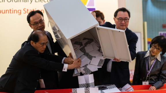 "HONG KONG, CHINA - NOVEMBER 24: Barnabus Fung (2nd R) and Patrick Nip Tak-kuen (2nd L) empty a ballot box to count votes at a polling station on November 24, 2019 in Hong Kong, China. Hong Kong held its district council election on Sunday as anti-government protests continue into a sixth month, with demands for an independent inquiry into police brutality, the retraction of the word ""riot"" to describe the rallies, and genuine universal suffrage. (Photo by Billy H.C. Kwok/Getty Images)"