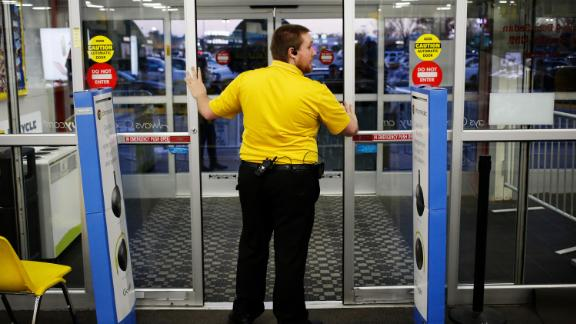 An employee prepares to open the entrance doors to a Best Buy Co. store ahead of Black Friday in Chesapeake, Virginia, U.S., on Thursday, Nov. 26, 2015. In 2011, several big U.S. retailers moved their opening times to midnight; in 2012, Wal-Mart crossed the Rubicon and opened its stores at 8 p.m. on Thanksgiving Day. But after last year