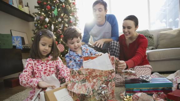 A stock photo shows parents watching children open Christmas gifts.