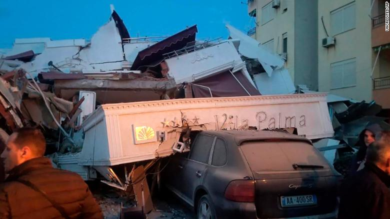 A car is buried beneath debris at a hotel in Durres.