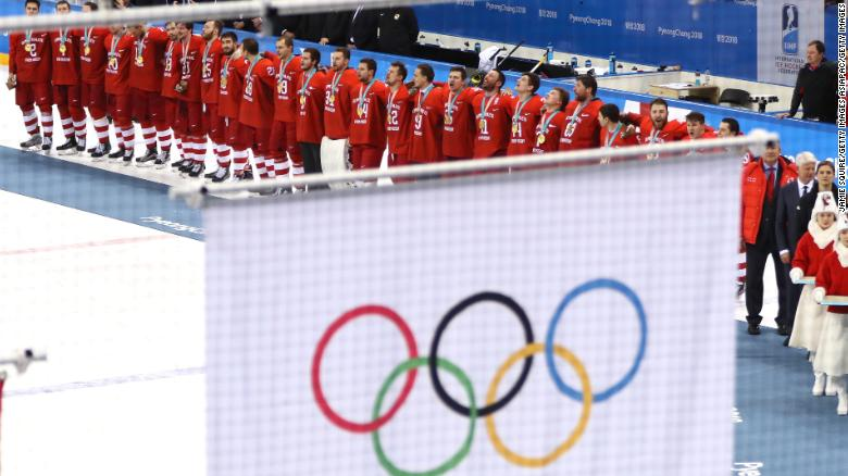 Russian athletes competing under  a neutral banner look on as the Olympic flag is raised during the medal ceremony at PyeongChang 2018.