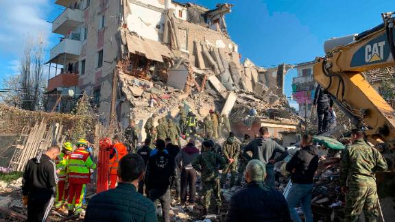 Emergency responders work in the rubble of a damaged building.