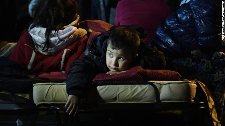 A boy rests in a portable bed in a camp that was set up at a soccer stadium in Durres.