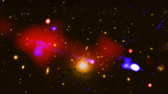 This image, which combines observations from the Chandra X-ray Observatory and the Karl Jansky Very Large Array, shows a black hole that is triggering star formation nearly one million light-years away from it. The large red bubble on the left is a hot gas bubble and the dots of light to the right of it are four galaxies where star formation has increased. The host galaxy of the black hole that released the gas bubble is the bright point of light to the right of the golden light at the center.