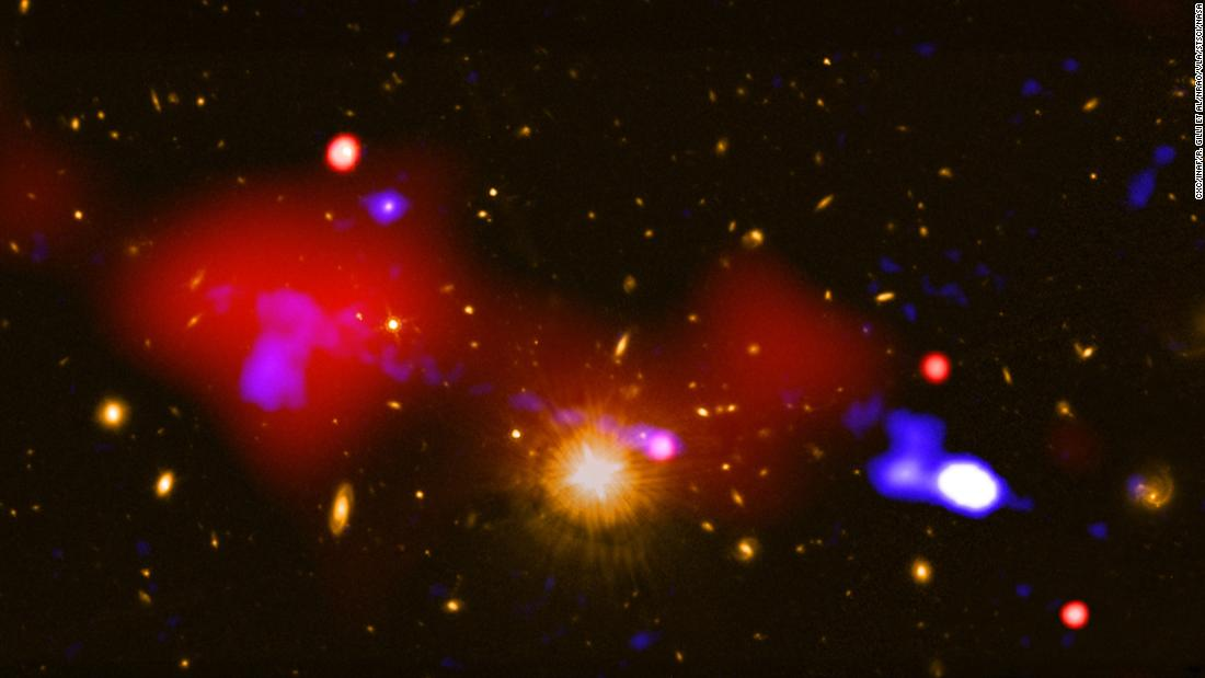 "This <a href=""https://chandra.harvard.edu/photo/2019/bhfeedback/"" target=""_blank"">image</a>, which combines observations from the Chandra X-ray Observatory and the Karl Jansky Very Large Array, shows a black hole that is triggering star formation nearly one million light-years away from it. The large red bubble on the left is a hot gas bubble and the dots of light to the right of it are four galaxies where star formation has increased. The host galaxy of the black hole that released the gas bubble is the bright point of light to the right of the golden light at the center."