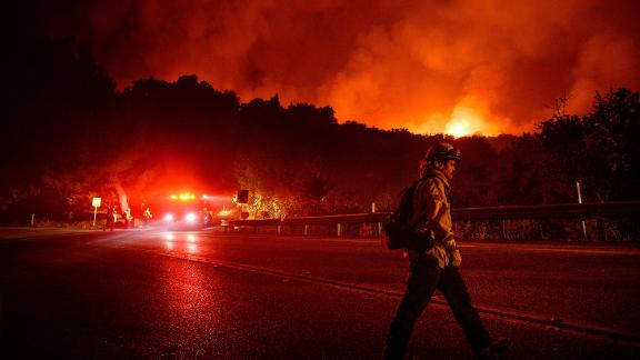 A firefighter crosses Highway 154 while battling the Cave Fire in Los Padres National Forest.
