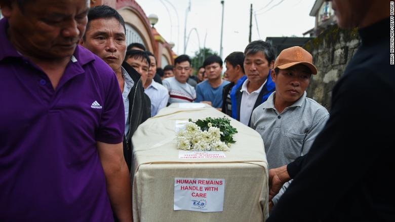 Relatives carry the casket bearing the body of migrant Nguyen Van Hung on arrival in Hanoi on November 27, 2019.