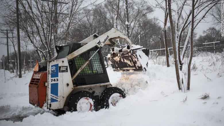 A man plows snow Wednesday after a blizzard struck Minneapolis.