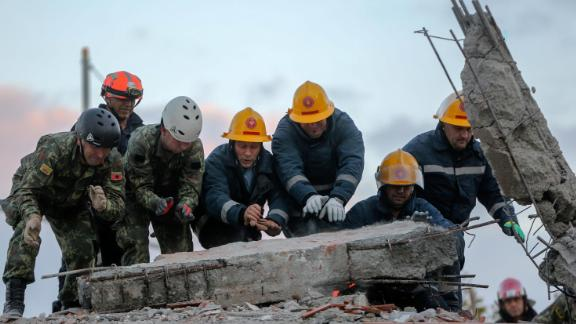 Members of the emergency services work to remove debris from a damaged building in Durres.