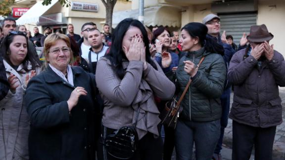 People grieve at the site of the disaster in Durres.