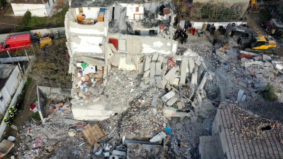 An aerial photo taken on Wednesday, November 27, shows emergency crews searching the rubble of a collapsed building in Thumane, Albania, the day after a devastating earthquake struck the region.