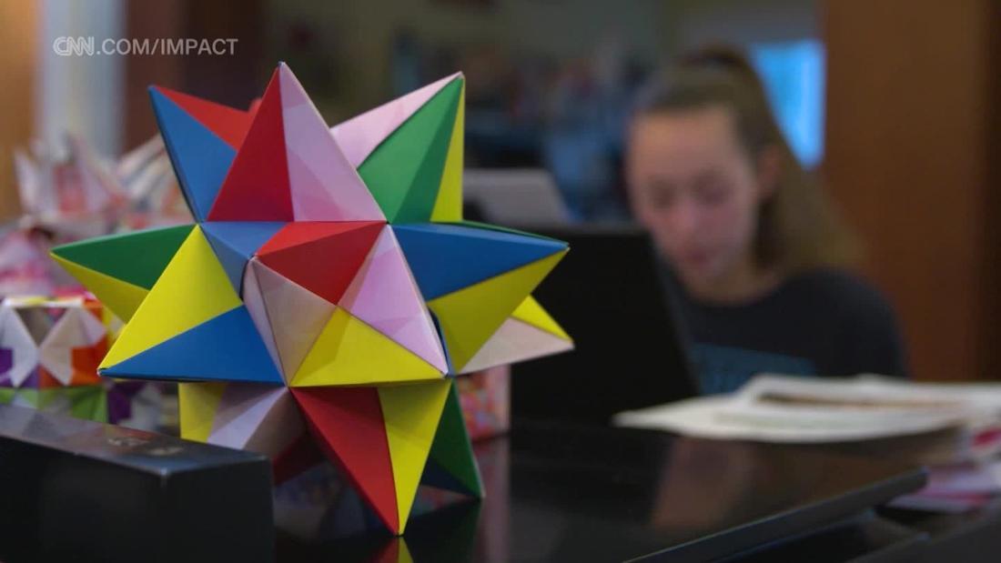 Die Schwestern drehen origami in einer Weise, um Leben zu retten