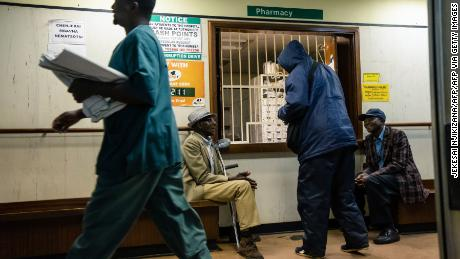 Elderly men wait for medicines at a pharmacy at Parirenyatwa hospital in Harare September 9, 2019. - For Zimbabwe's doctors, few institutions reflect their country's decay under Robert Mugabe than the once-vaunted public hospitals, now deteriorated, under-equipt and failing. In Zimbabwe, medics say, latex gloves serve as urine bags, operating rooms lack of light bulbs and patients are often forced to refuel their own ambulances. Mugabe, who died last week in Singapore at age 95, may have swept to power as a liberation hero, but his rule was marked by economic collapse that left his people scrambling to survive. Local doctors noted the symbolism of Mugabe seeking treatment 8,000 km from home in Singapore's modern Gleneagles clinic where a private suite can cost more than $1,000 a day. (Photo by Jekesai NJIKIZANA / AFP)        (Photo credit should read JEKESAI NJIKIZANA/AFP via Getty Images)