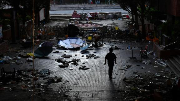 A man walks past debris littering the entrance at the Hong Kong Polytechnic University campus in the Hung Hom district of Hong Kong on November 27, 2019, over a week after police surrounded the building while protesters were still barricaded inside. - Teams at one of Hong Kong
