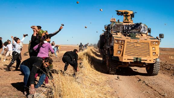 Kurdish demonstrators hurl rocks at a Turkish military vehicle on Friday, November 8, during a joint Turkish-Russian patrol near the town of Al-Muabbadah in the northeastern part of Hassakah on the Syrian border with Turkey.