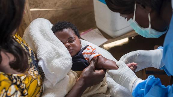 A nurse prepares to vaccinate an infant in North Kivu province, Democratic Republic of  Congo.